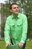 Young handsome man in a green shirt on the background of summer Stock Photos