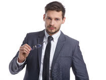 Young handsome man in grey suit and glasses smiling Stock Photos