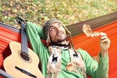 Young handsome man with guitar relax in a hammock in the autumn Royalty Free Stock Photography
