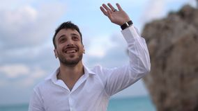 Young handsome man happily smiling with an amazed expression to others and waving hand. Cyprus. Paphos. Young handsome cute man happily smiling with an amazed stock video