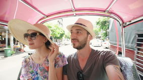 Young handsome man in hat with his girlfriend ride on traditional thai bus songteo . Couple travel Thailand during their. Young handsome man in hat with his stock video footage