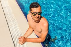 Man having a good time in swimming pool. All inclusive. Summer vacation concept. Young handsome man having a good time in swimming pool. All inclusive. Summer Stock Image
