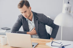 Young handsome man having heartache while working. Something with my heart. Handsome hardworking young man working on laptop and having heartache while sitting Royalty Free Stock Image