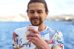 A young handsome man having hot coffee outside near the sea enjoying this moment Stock Photography