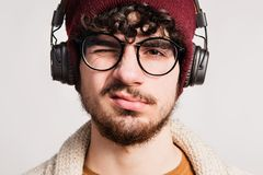 Portrait of a young man with headphones in a studio. A young handsome man with headphones in a studio, listening to music. Close up Royalty Free Stock Images