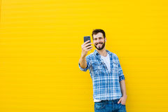 Young handsome man with headphones on yellow wall Royalty Free Stock Photos