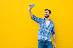 Young handsome man with headphones on yellow wall Royalty Free Stock Images