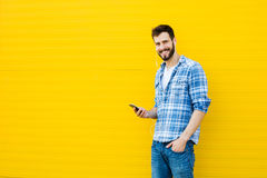 Young handsome man with headphones on yellow wall Stock Image