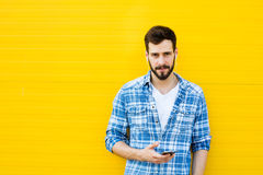 Young handsome man with headphones on yellow wall Royalty Free Stock Photography