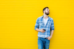Young handsome man with headphones on yellow wall Stock Images