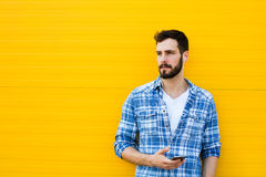 Young handsome man with headphones on yellow wall Royalty Free Stock Image