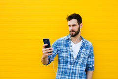 Young handsome man with headphones on yellow wall Stock Photos