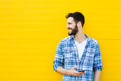 Young handsome man with headphones on yellow wall Stock Photography