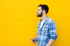 Young handsome man with headphones on yellow wall Stock Photo