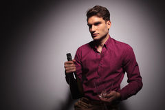 Young handsome man holding a bottle of wine Royalty Free Stock Images