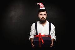Young handsome man holding christmas gift box over black background. Royalty Free Stock Photo