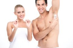 Young handsome man holding deodorant for armpits. royalty free stock image
