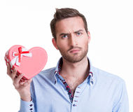 Young handsome man holding a gift. Stock Photos