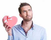 Young handsome man holding a gift. Royalty Free Stock Photo