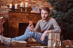 A young handsome man holding a phone and looking at a camera while sitting on a floor surrounded by gifts royalty free stock photos