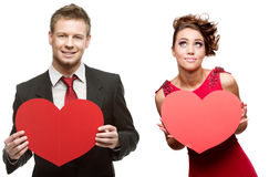 Young handsome man holding red heart and cheerful woman on white Royalty Free Stock Photography