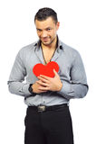 Young handsome man holding a red heart shaped toy Stock Photo