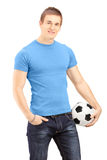 Young handsome man holding a soccer ball Stock Photography