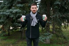 Young handsome man holding two cups of coffee. Royalty Free Stock Image