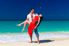 Young handsome man holds a beautiful brunette in a red dress on Stock Photography