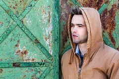 A young man in a hood. A young handsome man in a hood on the background of a rusty door Stock Image