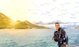 Young handsome man isolated diver smiling ready to go scuba diving in cold water wet suit, fins, weight belt & oxigen. Young handsome man isolated diver smiling stock photo