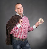 Young handsome man with jacket and money. On a gray background Stock Photography