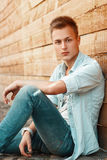 Young handsome man in jeans clothes sitting near a wooden wall. Denim Stock Image