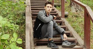 Young man sitting on stairs in forest stock video footage