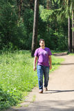 Young handsome man in jeans walks on path Stock Images