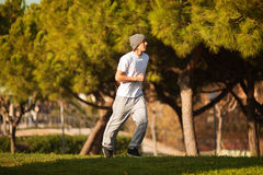 Young handsome man jogging in public park Stock Photos