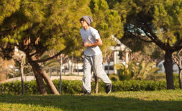 Young handsome man jogging in public park Royalty Free Stock Image