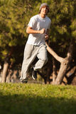Young handsome man jogging in public park Royalty Free Stock Images