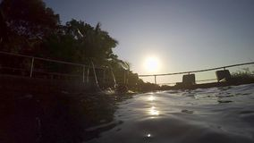 Young handsome man jumping into swimming pool during amazing sunset. 1920x1080 stock video footage