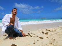 Young handsome man kneeling by beach Stock Image
