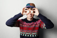 Young handsome man in knit colourful clothes. Gray wall behind Royalty Free Stock Photos