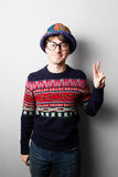 Young handsome man in knit colourful clothes. Gray wall behind Royalty Free Stock Photo
