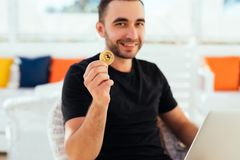Young handsome man with laptop pointed bitcoin on camera sitting on deck at beack cafe on summer vocation. Man check bitcoin value. Young handsome man with Stock Images