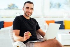 Young handsome man with laptop pointed bitcoin on camera sitting on deck at beack cafe on summer vocation. Man check bitcoin value. Young handsome man with Royalty Free Stock Image