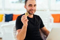 Young handsome man with laptop pointed bitcoin on camera sitting on deck at beack cafe on summer vocation. Man check bitcoin value. Young handsome man with Stock Image