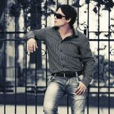 Young handsome man leaning on cast iron fence Royalty Free Stock Image