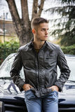 Young handsome man leaning on his new car Royalty Free Stock Image