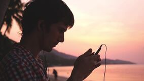 Young handsome man holds mobile phone listens to music on tropical beach during amazing sunset. Slow motion. 1920x1080. Young handsome man listen to music and stock footage