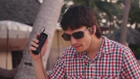 Young handsome stylish man in sunglasses listen to music and dance on tropical beach at sunset time. Slow motion. Young handsome man listen to music and dance on stock video footage