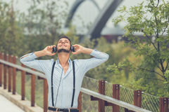 Young handsome man listening to music in an urban context Royalty Free Stock Photos
